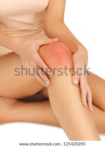 closeup picture of female hands touching knee - stock photo