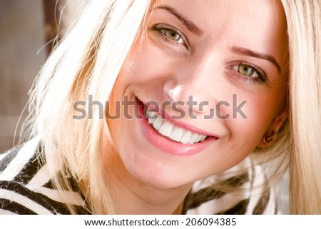 closeup picture of green eyes pinup girl beautiful blond young woman having fun happy smiling showing great dental whitening teeth & looking at camera  - stock photo