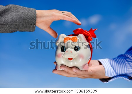 Closeup picture of hands holding piggy bank over blue sky sunny outdoors background - stock photo