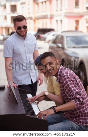 Closeup picture of keyboard of piano. Afro-american man playing piano and look at camera while his best friends standing near him. - stock photo