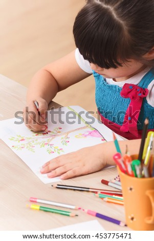 Closeup picture of little girl drawing picture with multicoloured pencils while sitting at the table at home. - stock photo