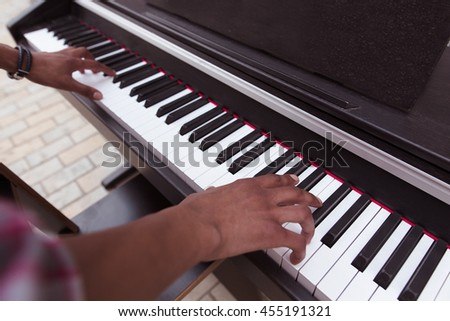 Closeup picture of of keyboard of piano. Black man playing piano outdoors in city centr. Professional musician playing piano. - stock photo