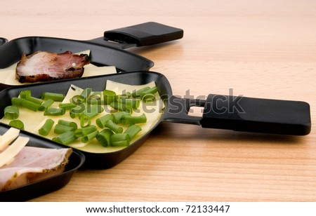 Closeup picture of raclette pan with cheese, becon and spring onion - stock photo