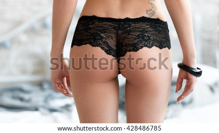 Closeup picture of woman buttocks in black lace panties . Extreme closeup of sexy woman ass. Perfect buttocks in black lace lingerie. - stock photo