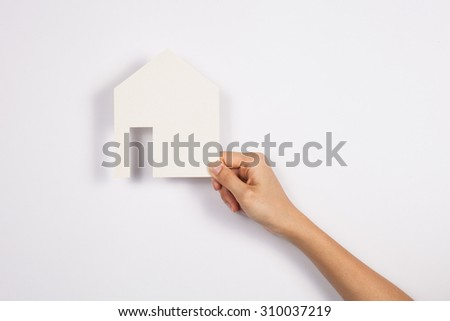 closeup picture of woman hands holding white paper house - stock photo