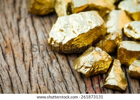 closeup pile of gold nugget on wooden table  - stock photo