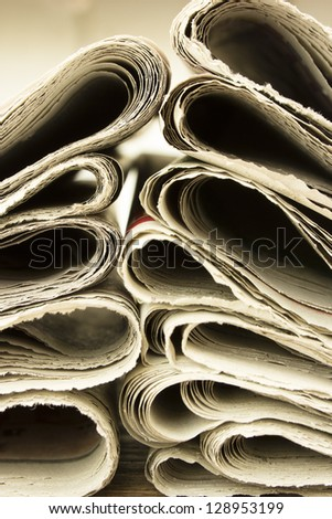 closeup pile of newspaper on wooden background - stock photo