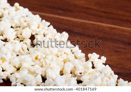 Closeup pile of white fluffy popcorn lying mixed together on wooden surface