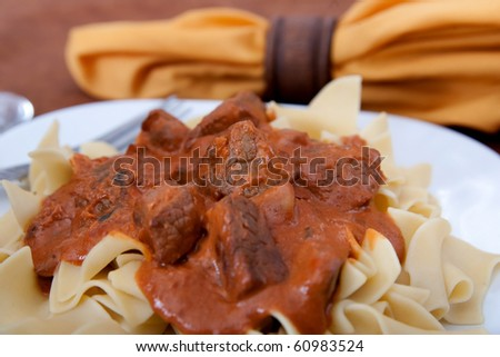 closeup plate of beef stroganoff over egg noodles with sauce - stock photo