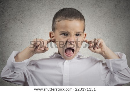 Closeup portrait angry annoyed pissed off boy plugs his ears with fingers sticking out tongue looking with funny negative facial expression, disapproval isolated grey wall background. Human emotions - stock photo