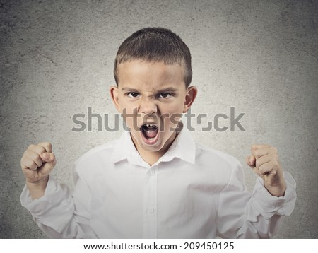 Closeup Portrait Angry child, Boy Screaming fists up in air, demanding justice, his rights isolated grey wall background. Negative human Emotion, Facial Expression, body language, attitude, perception - stock photo