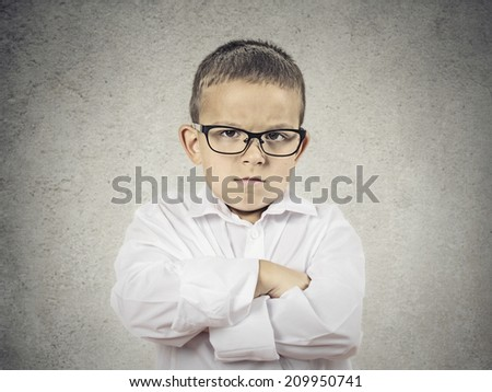 Closeup portrait Angry, displeased child Boy looking at you camera, arms folded, insists on his position isolated grey wall background. Negative human emotions, feelings, facial expression, perception - stock photo