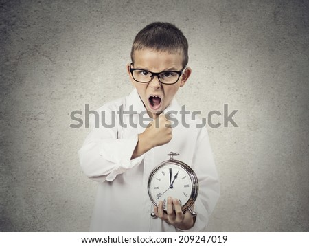 Closeup portrait, Angry, Mad, pissed off Child, Boy, playing boss manager, Screaming, about to smash alarm clock with fist, isolated grey wall background. Negative human emotions, facial expressions - stock photo