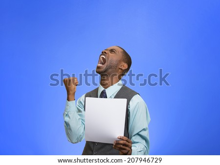 Closeup portrait angry, mad, screaming business man holding paper, document, screaming, looking up isolated blue background. Negative emotions, facial expression, feeling. Financial crisis, bad news - stock photo