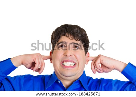 Closeup portrait, angry, unhappy, irritated young man covering ears, looking up, thinking stop making loud noise giving me headache, isolated white background. Negative emotion, face expression - stock photo