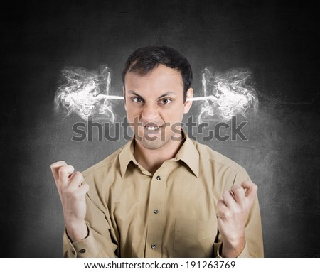 Closeup portrait angry young man, blowing steam coming out of ears, about to have nervous atomic breakdown, isolated black background. Negative human emotions, facial expressions, feelings, attitude - stock photo