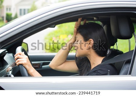 Closeup portrait, angry young sitting woman pissed off by drivers in front of her, hand on head, isolated city street background. Road rage traffic jam concept - stock photo