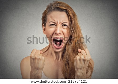Closeup portrait angry young woman hysterical having nervous atomic breakdown, screaming, fists up in air isolated grey wall background. Negative human emotion facial expression feeling bad attitude - stock photo