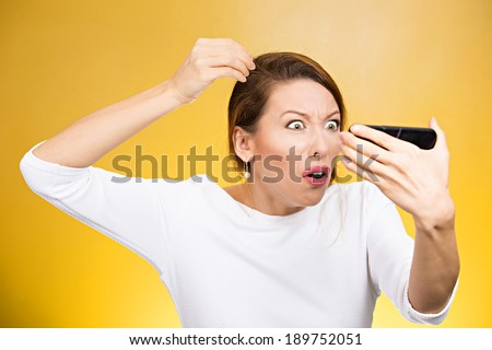 Closeup portrait, annoyed woman looking worried at white color hair or balding, isolated yellow background. Negative human emotion facial expression feelings, attitudes, reaction, situation - stock photo