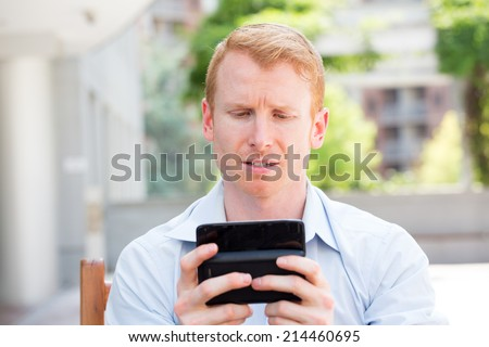 Closeup portrait, annoyed young man in blue shirt, pissed off by what he heard or sees on his cell phone, isolated outdoors outside background - stock photo
