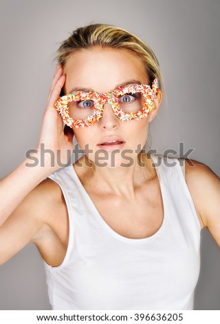 Closeup portrait anxious young blonde girl surprising emotion on her face, hands on head, in funny colorful handmade glasses, isolated studio background. Human emotion, reaction, expression - stock photo