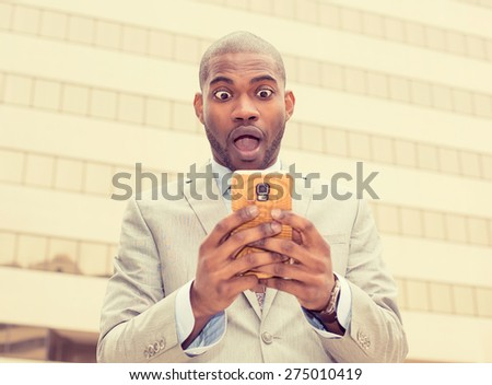 Closeup portrait anxious young business man looking at phone seeing bad news or photos with disgusting emotion on his face isolated outside city background. Human emotion, reaction, expression - stock photo