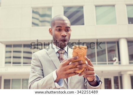 Closeup portrait anxious young business man looking at smart phone seeing bad news or photos with disgusting shocked face expression isolated outside city background. Human emotion, reaction - stock photo