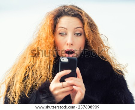 Closeup portrait anxious young girl looking at phone seeing bad news or photos with disgusting emotion on her face isolated outside sky background. Human emotion, reaction, expression - stock photo