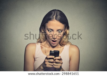 Closeup portrait anxious young girl looking at phone seeing bad news or photos with shocked disgusting emotion on her face isolated on gray wall background. Human reaction, expression - stock photo