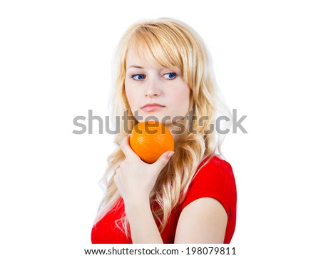 Closeup portrait attractive blonde young woman holding orange, thinking, isolated white background. Diet. Dieting concept. Healthy Food, life style. Choice between fruits and sweets. Weight Loss - stock photo