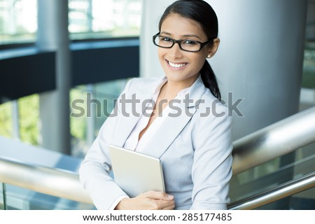 Closeup portrait, attractive happy woman in gray white suit and black glasses holding silver pc, isolated indoors interior office background. Positive human emotion facial expressions feelings - stock photo