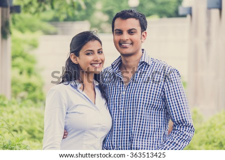 Closeup portrait, attractive wealthy successful couple in blue shirt and striped outfit holding each other smiling, isolated outside green trees background. - stock photo
