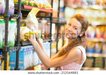 Closeup portrait Beautiful attractive young, happy, smiling Woman shopping for cereal, bulk in grocery supermarket. Positive facial expressions, emotions, feelings. Customer satisfaction concept - stock photo