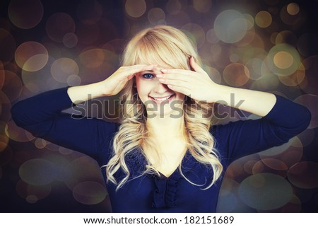 Closeup portrait beautiful, blonde, young woman, covering her eyes with hands, smiling, secretly looking at you one palm raised, isolated kaleidoscope background. Positive emotions, face expressions - stock photo