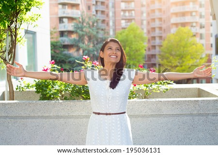 Closeup portrait, beautiful happy, gorgeous young female relaxing on a balcony on a sunny summer day, enjoying her weekend, background of a city building scenery and green trees. Urban lifestyle. - stock photo