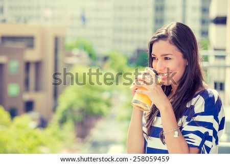 Closeup portrait beautiful happy woman enjoying sunny day off on a balcony of her apartment drinking orange juice on a urban city background. Positive face expressions emotions healthy lifestyle  - stock photo