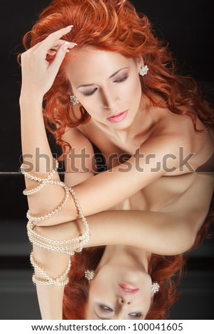closeup portrait beautiful redhead young woman with mirror and pearl necklace on her hand - stock photo