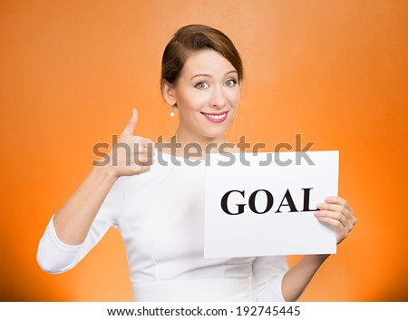 Closeup portrait beautiful smiling, happy business woman holding sign goal, giving thumbs up isolated orange background. Positive emotions, facial expressions, reaction, attitude, determination  - stock photo
