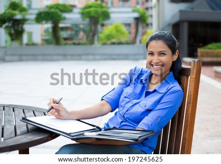 Closeup portrait, beautiful, smiling young business woman in blue shirt, sitting, taking notes outside, isolated trees background - stock photo
