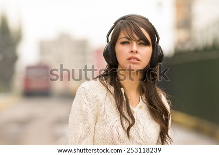 closeup portrait beautiful young girl walking in the streets af city wearing headphones