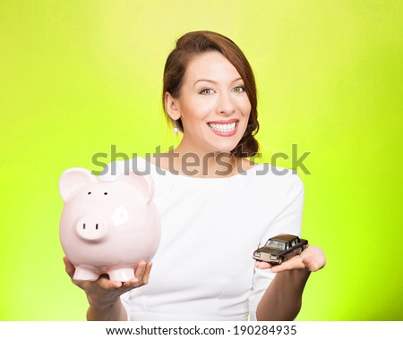 Closeup portrait, beautiful, young woman, dealership agent holding model black car, pink piggy bank in hand, offering credit line, isolated green background. Lease, automobile purchase, financing.