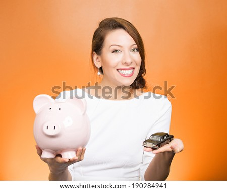 Closeup portrait, beautiful, young woman, dealership agent holding model black car, pink piggy bank in hand, offering credit line, isolated orange background. Lease, automobile purchase, financing.