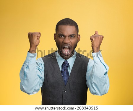Closeup portrait bitter mad displeased pissed off angry grumpy corporate man open mouth hands fist in air screaming yelling isolated yellow background. Negative human emotion facial expression feeling - stock photo