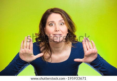 Closeup portrait cautious, afraid, serious, annoyed displeased young woman raising hands up to say no, stop right there isolated green background. Negative human emotion facial expression sign symbol - stock photo