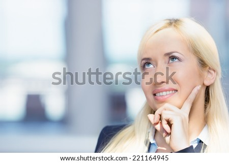 Closeup portrait charming, smiling joyful happy business woman looking upwards daydreaming something, thinking isolated background corporate office windows. Positive human emotions, facial expression - stock photo
