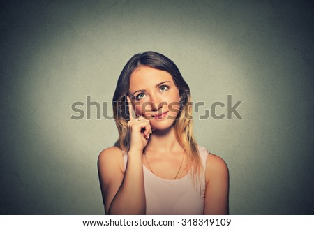 Closeup portrait charming smiling joyful happy young woman looking upwards daydreaming something nice isolated gray wall background. Positive human emotions facial expressions feelings perception  - stock photo
