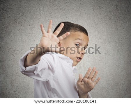 Closeup portrait child boy looking shocked scared trying to protect himself from unpleasant situation, object thrown at him isolated grey wall background. Negative emotion facial expression feeling - stock photo