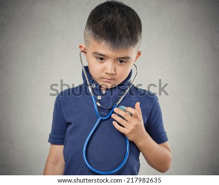 Closeup portrait child little boy listening to his heart with stethoscope isolated grey wall background. Children healthcare medical care, preventive medicine, self assessment concept. Face expression - stock photo