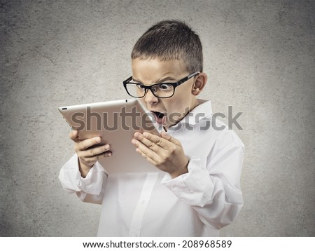 Closeup portrait child, shocked, surprised, funny looking boy with glasses using, holding laptop, pad computer isolated grey, black background. Human face expressions, emotions, reaction body language - stock photo