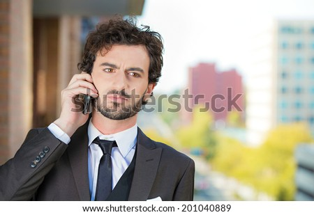 Closeup portrait, classy looking, handsome young, serious, worried business man talking on cell phone on balcony his apartment isolated city background. Urban life style, corporate professional worker - stock photo